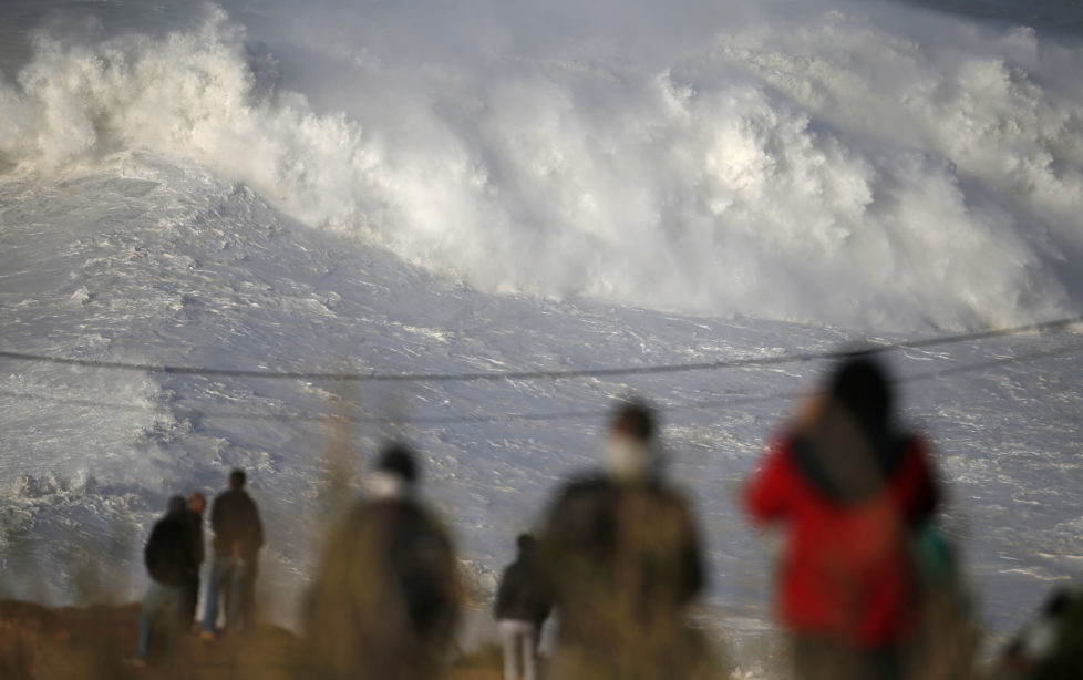 People gather to watch a tow-in surfing session at Praia do Norte, in Nazare December 11, 2014. Praia do Norte beach has gained popularity with big wave surfers since Hawaiian surfer Garrett McNamara broke a world record for the largest wave surfed here in 2011. REUTERS/Rafael Marchante (PORTUGAL - Tags: SPORT ENVIRONMENT) - RTR4HOLE
