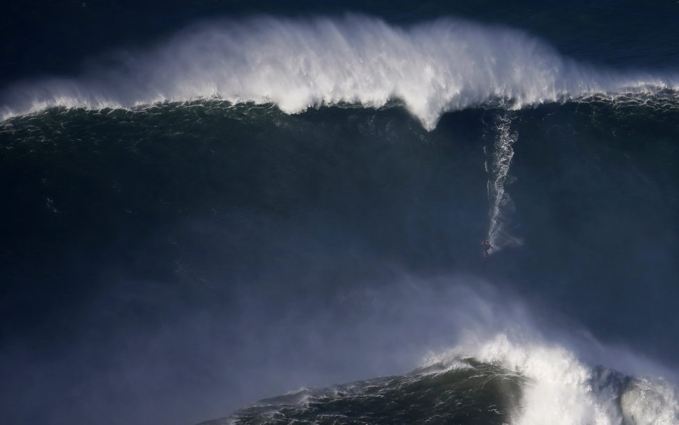 A surfer drops in on a large wave at Praia do Norte, in Nazare December 11, 2014. Praia do Norte beach has gained popularity with big wave surfers since Hawaiian surfer Garrett McNamara broke a world record for the largest wave surfed here in 2011. REUTERS/Rafael Marchante (PORTUGAL - Tags: SPORT TPX IMAGES OF THE DAY) - RTR4HO6I
