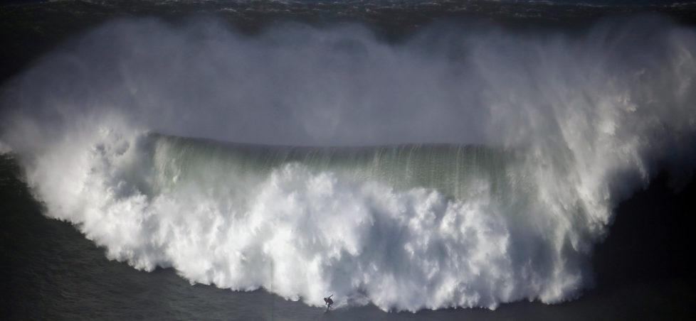 A surfer drops in on a large wave at Praia do Norte, in Nazare December 11, 2014. Praia do Norte beach has gained popularity with big wave surfers since Hawaiian surfer Garrett McNamara broke a world record for the largest wave surfed here in 2011. REUTERS/Rafael Marchante (PORTUGAL - Tags: SPORT ENVIRONMENT) - RTR4HOKD