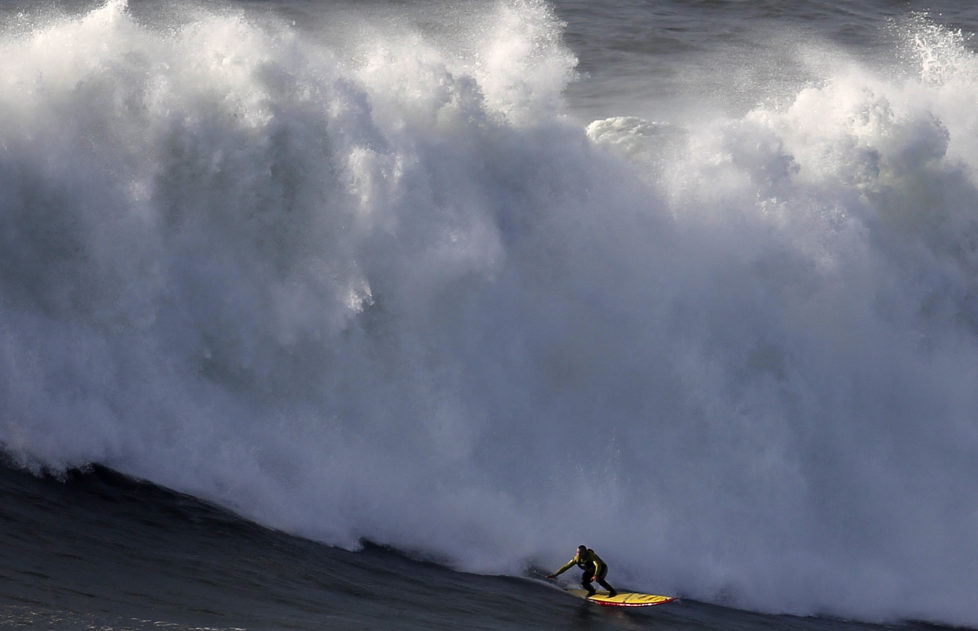 Big-wave surfer Garrett McNamara drops in on a large wave at Praia do Norte in Nazare January 29, 2013. McNamara of Haleiwa, Hawaii, who won the Biggest Wave title at the 2012 Billabong XXL Big Wave Awards with his world record 78-foot (24-metre) wave ridden at Praia do Norte on November 1, 2011. McNamara has returned to Nazare because he wants to try to beat the record again, and the forecast for the next days are of big waves. REUTERS/Rafael Marchante (PORTUGAL - Tags: SPORT TPX IMAGES OF THE DAY) - RTR3D4NV