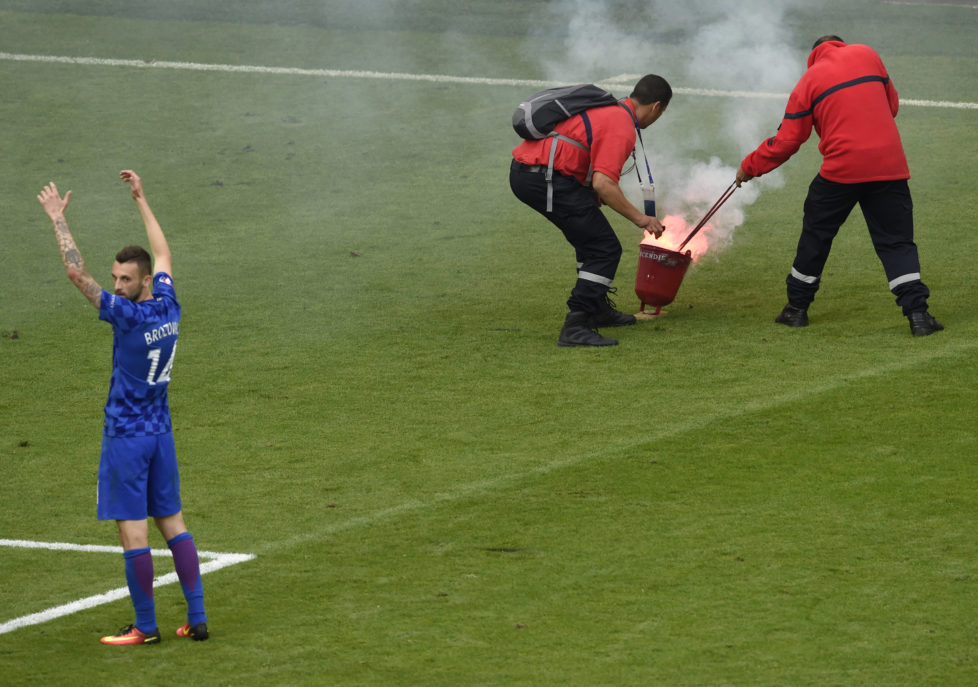 Croatia's midfielder Marcelo Brozovic reacts as firefighter extinguish a flare during the Euro 2016 group D football match between Czech Republic and Croatia at the Geoffroy-Guichard stadium in Saint-Etienne on June 17, 2016. Czech Republic and Croatia drew 2-2. / AFP PHOTO / JEAN-PHILIPPE KSIAZEK