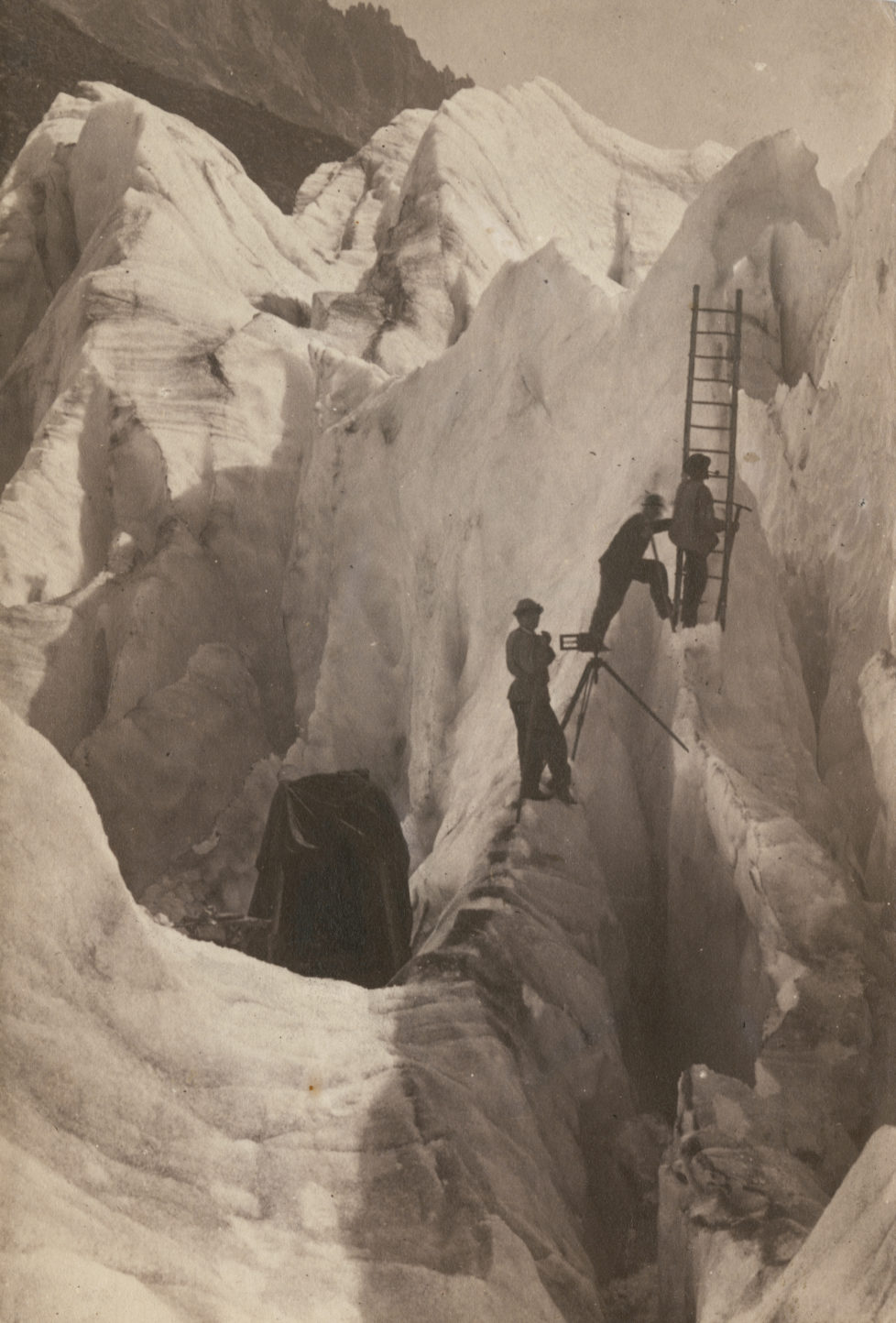 A photographer with his glass plate camera mounted on a tripod straddling a crevasse, and two assistants setting up a ladder, on a glacier in the Alps, circa 1880. The object on the left is possibly a light-proof tent used for coating and developing wet plates. (Photo by Hulton Archive/Getty Images)