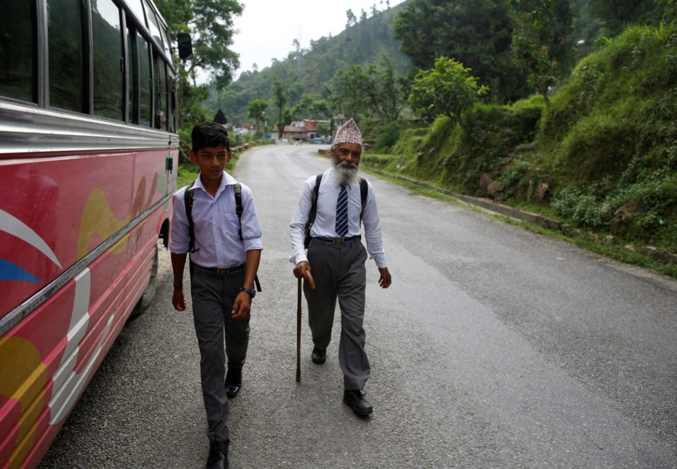 """Durga Kami, 68, who is studying tenth grade at Shree Kala Bhairab Higher Secondary School, walks with his classmate Sagar Thapa, 14, as they head to school in Syangja, Nepal, June 5, 2016. REUTERS/Navesh Chitrakar. SEARCH """"DURGA KAMI"""" FOR THIS STORY. SEARCH """"THE WIDER IMAGE"""" FOR ALL STORIES"""