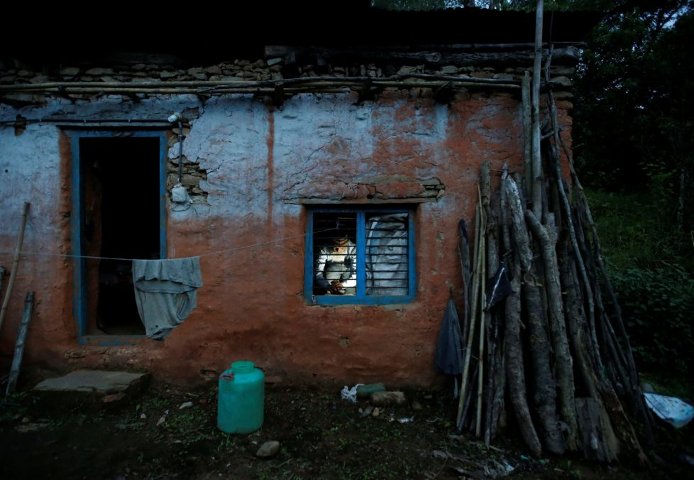 """Durga Kami, 68, who is studying in the tenth grade at Shree Kala Bhairab Higher Secondary School, is seen through the window as he prepares dinner for himself at his one room house in Syangja, Nepal, June 4, 2016. REUTERS/Navesh Chitrakar. SEARCH """"DURGA KAMI"""" FOR THIS STORY. SEARCH """"THE WIDER IMAGE"""" FOR ALL STORIES. TPX IMAGES OF THE DAY"""