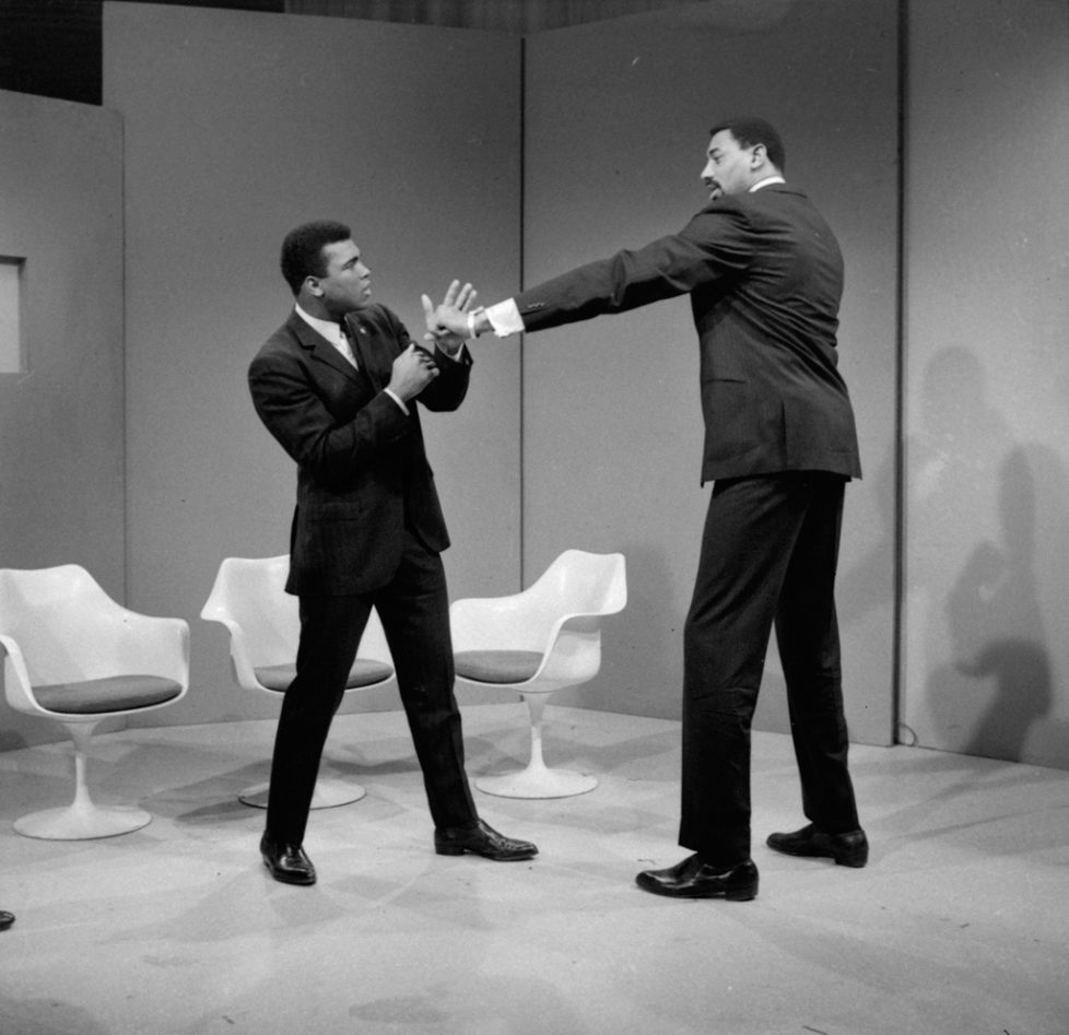 FILE - In this March 10, 1967 file photo, basketball star Wilt Chamberlain extends a long left towards world heavyweight boxing champion Muhammad Ali at an ABC television studio in New York. Chamberlain is 7 feet, 1 inch tall, and Ali is 6 feet, 2 inches with Chamberlain's reach over 90 inches against Ali's 79 inches. (AP Photo)