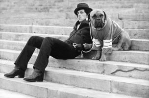 American actor Sylvester Stallone sits on a staircase while holding the leash of a dog wearing a football jersey in a still from the film, 'Rocky,' directed by John G. Avildsen, 1976. (Photo by United Artists/Courtesy of Getty Images)