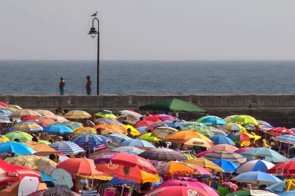 Fotowettbewerb KW 30 - Hitze Der Sonnenschirmwald als willkommener Schattenspender. Diese bunten «Tupfer» und die Weite des Meeres für mich ein feines Kontrastprogramm. Fotografiert in Cadiz (Andalusien).