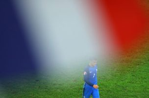 France's Antoine Griezmann is seen through a French flag waved by a spectator as he celebrates after scoring the opening goal during the Euro 2016 semifinal soccer match between Germany and France, at the Velodrome stadium in Marseille, France, Thursday, July 7, 2016. (AP Photo/Thibault Camus)