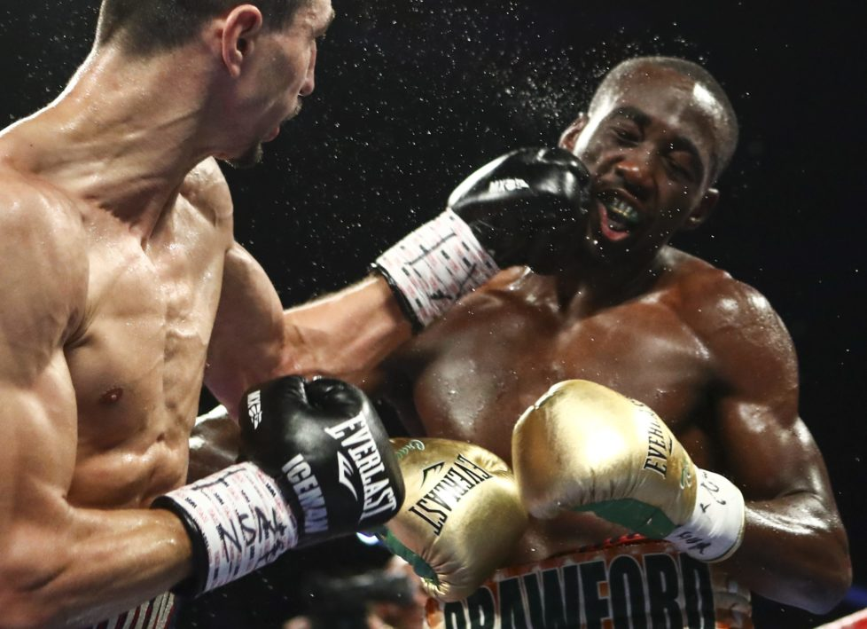 Viktor Postol, left, hits Terence Crawford during their WBC-WBO junior welterweight title unification boxing bout in Las Vegas on Saturday, July 23, 2016. (AP Photo/Chase Stevens)