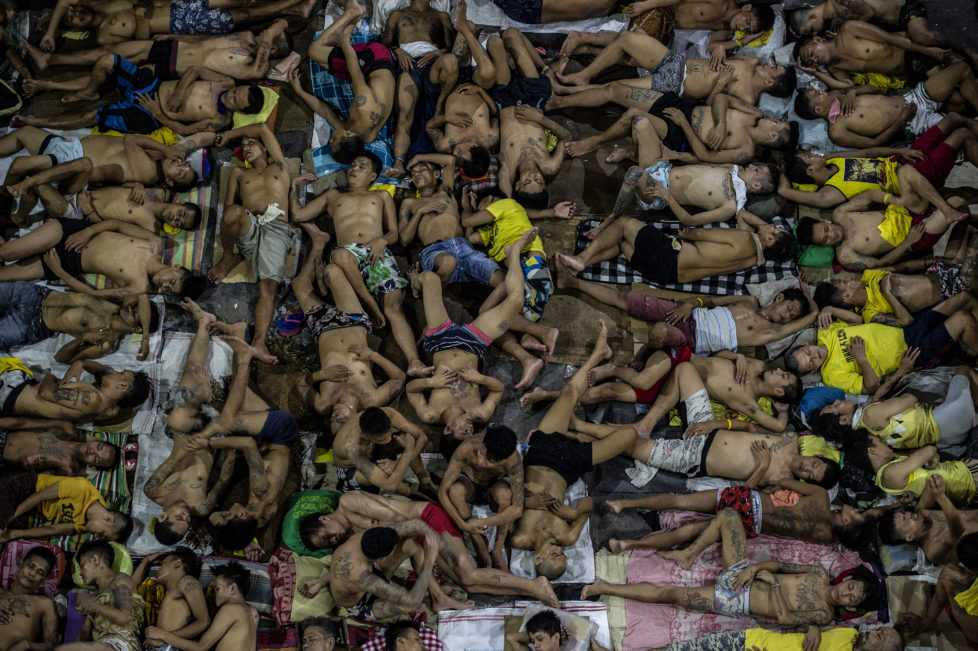 In this photo taken on July 19, 2016 inmates sleep on the ground of an open basketball court inside the Quezon City jail at night in Manila. There are 3,800 inmates at the jail, which was built six decades ago to house 800, and they engage in a relentless contest for space. Men take turns to sleep on the cracked cement floor of an open-air basketball court, the steps of staircases, underneath beds and hammocks made out of old blankets. / AFP PHOTO / NOEL CELIS / TO GO WITH AFP STORY: Philippines-politics-crime-jails, FOCUS by Ayee Macaraig