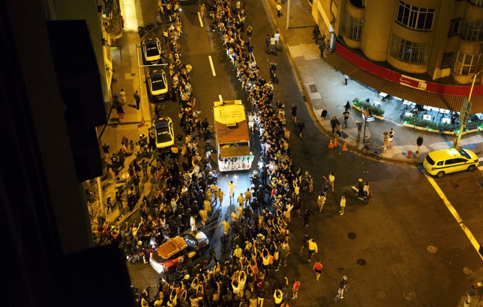 The Olympic torch is carried through the streets of Copacabana as the torch relay continues on its journey to the opening ceremony of the 2016 Summer Olympics in Rio de Janeiro, Brazil, early Friday, Aug. 5, 2016. (AP Photo/David Goldman)