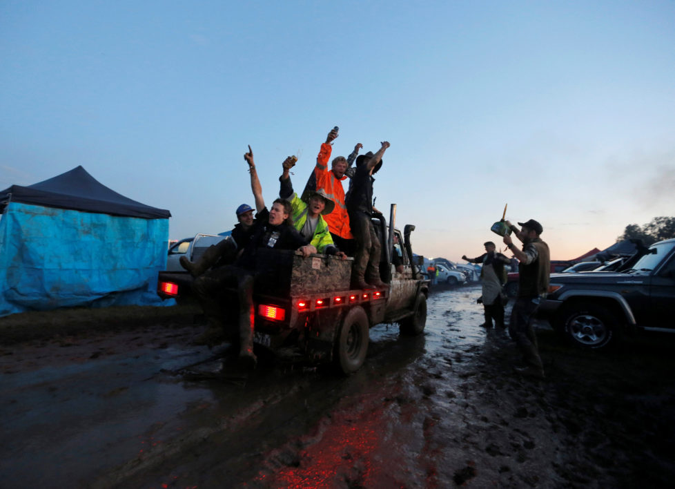 "Men ride on the back of a truck driving through mud on the final night of the Deni Ute Muster in Deniliquin, New South Wales, Australia, October 1, 2016. REUTERS/Jason Reed SEARCH ""UTE CULTURE"" FOR THIS STORY. SEARCH ""THE WIDER IMAGE"" FOR ALL STORIES."