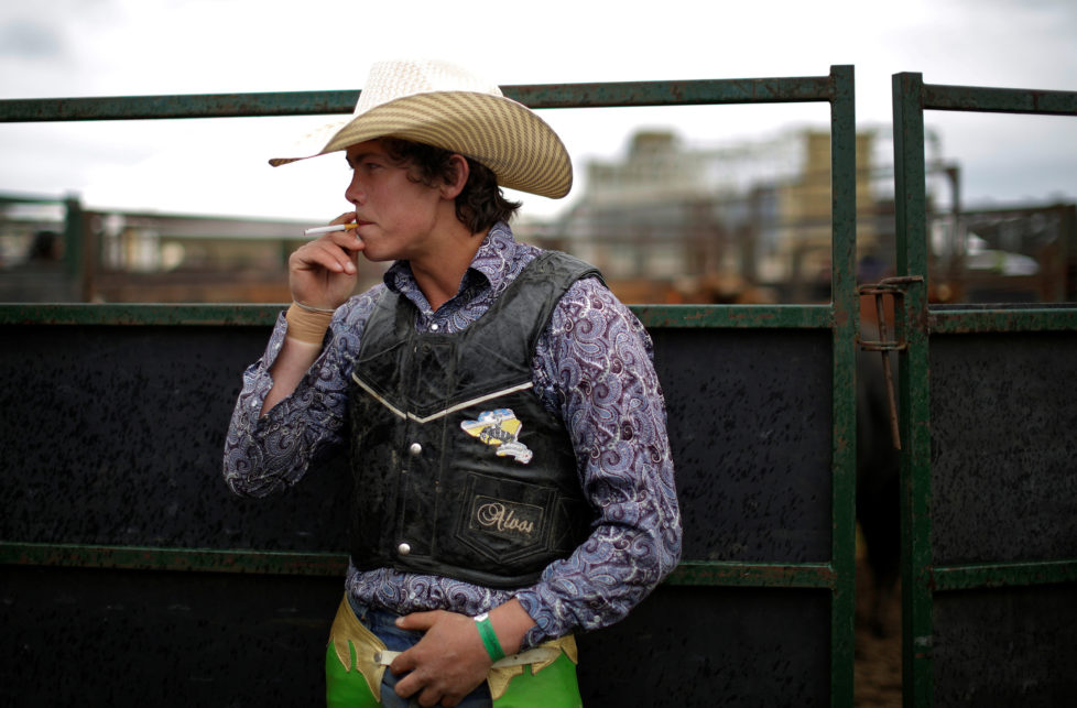 "Bull rider Tom Phibbs, 21, from Chiltern, smokes a cigarette before competing at the Deni Ute Muster in Deniliquin, New South Wales, September 30, 2016. REUTERS/Jason Reed SEARCH ""UTE CULTURE"" FOR THIS STORY. SEARCH ""THE WIDER IMAGE"" FOR ALL STORIES."
