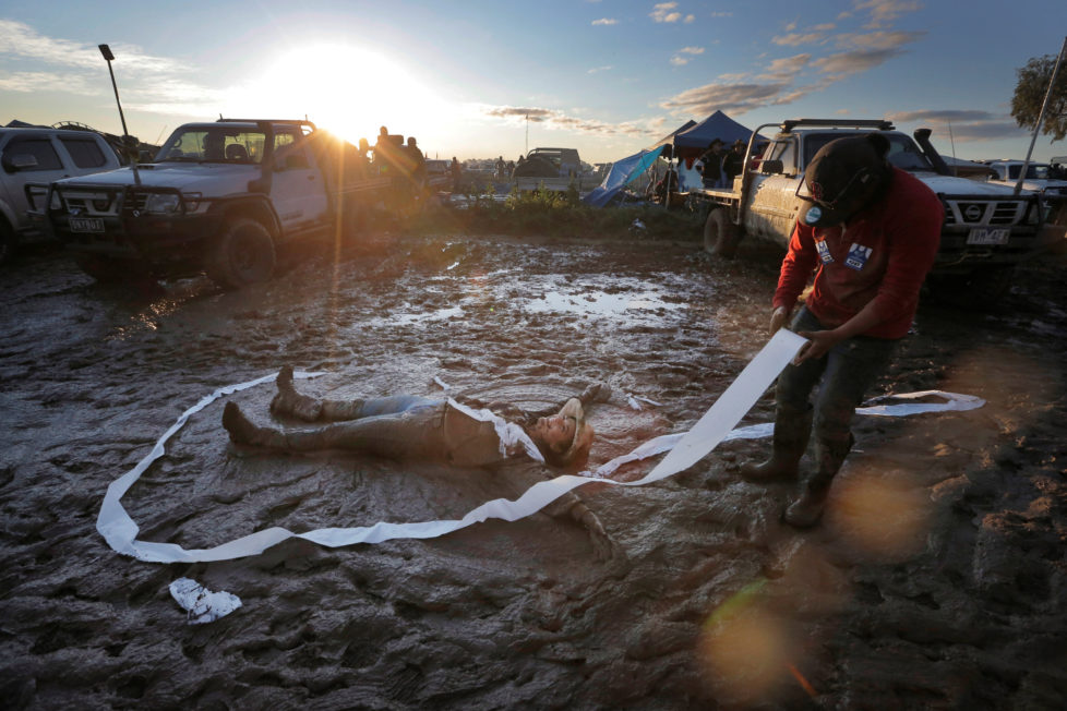 "Jess Elderedge makes a 'mud angel' as a friend lays toilet paper around her during a party at sunset on the final night of the Deni Ute Muster in Deniliquin, New South Wales, Australia, October 1, 2016. REUTERS/Jason Reed SEARCH ""UTE CULTURE"" FOR THIS STORY. SEARCH ""THE WIDER IMAGE"" FOR ALL STORIES."