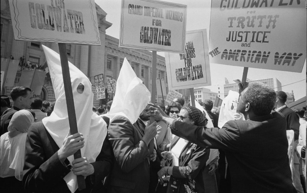 Ku Klux Klan members supporting Barry Goldwater's campaign for the presidential nomination at the Republican National Convention, as an African American man pushes signs back, San Francisco, California, July 12, 1964. (Photo by Warren K Leffler/PhotoQuest/Getty Images)