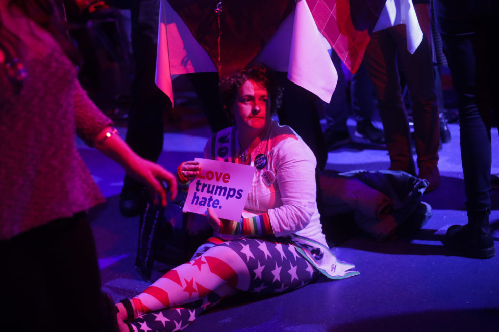 A woman sits on the floor to look the television screening at the presidential election night party of the Democrats Abroad in Berlin, Tuesday, Nov. 8, 2016. (AP Photo/Markus Schreiber).