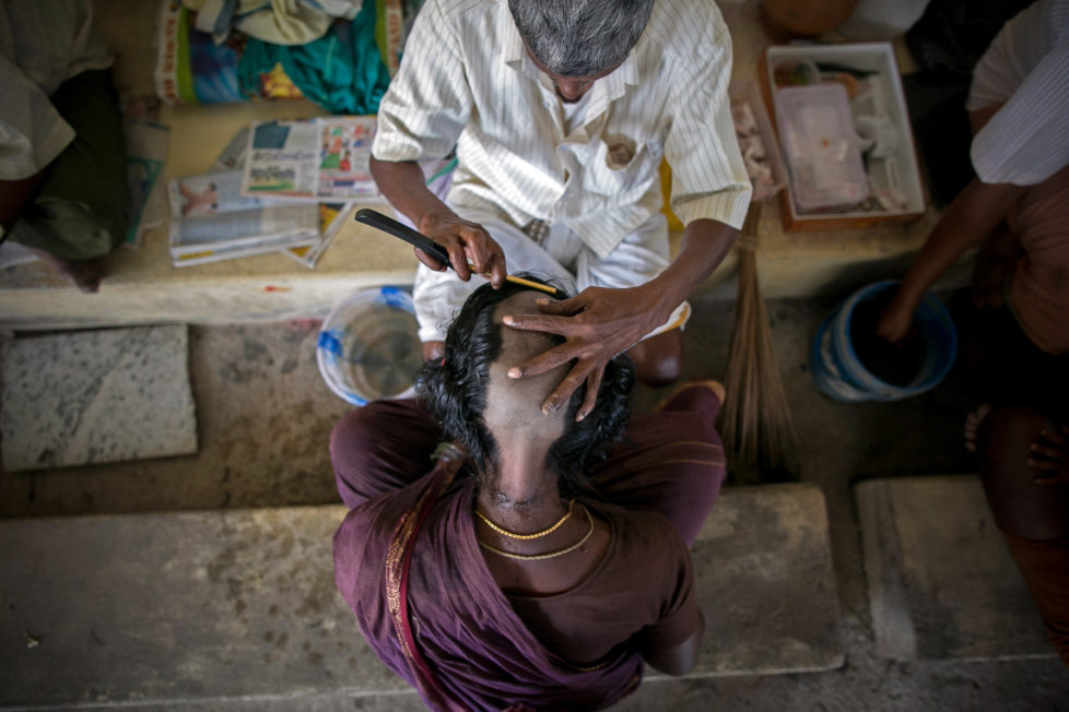 "THIRUTTANI, INDIA - NOVEMBER 10: 59 year old Laksmi has her head shaved at the Thiruthani Murugan Temple November 10, 2016 in Thiruttani, India. Her daughter was sick but she got better, so she wanted to show the Gods her gratitude by shaving her head. The process of shaving ones hair and donating it to the Gods is known as tonsuring. It is common for Hindu believers to tonsure their hair at a temple as a young child, and also to celebrate a wish coming true, such as the birth of a baby or the curing of an illness. The ""temple hair"", as it's known, is then auctioned off to a processing plant and then sold as pricey wigs and weaves in the US, Europe and Africa. (Photo by Allison Joyce/Getty Images)"
