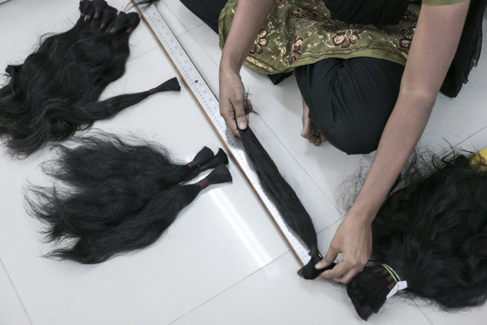 "CHENNAI, INDIA - NOVEMBER 11: A worker measures hair Raj Hair International November 11, 2016 in Thiruttani, India. Raj Hair International donates wigs to cancer patients in India and also exports hair products, including weaves and wigs, to 56 countries. All of the hair they export comes from Tamil Nadu, 1/4 of which is temple hair and the rest comes from comb waste that people sell. They estimate that it takes 1 full month to make one wig by hand. The process of shaving ones hair and donating it to the Gods is known as tonsuring. It is common for Hindu believers to tonsure their hair at a temple as a young child, and also to celebrate a wish coming true, such as the birth of a baby or the curing of an illness. The ""temple hair"", as it's known, is then auctioned off to a processing plant and then sold as pricey wigs and weaves in the US, Europe and Africa. (Photo by Allison Joyce/Getty Images)"