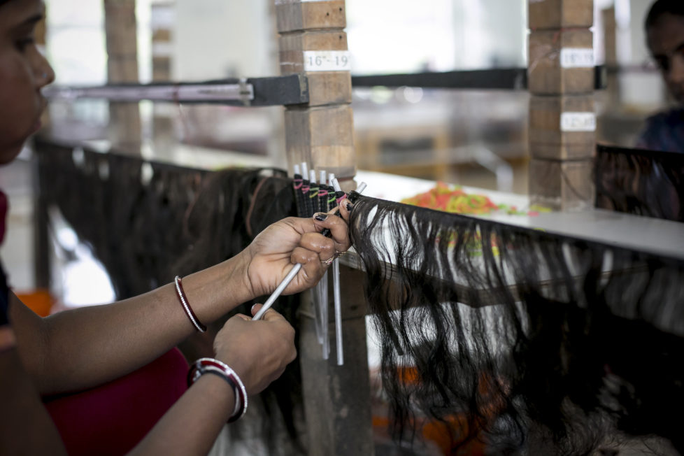 "CHENNAI, INDIA - NOVEMBER 11: A worker processes hair into a curly style at Raj Hair International November 11, 2016 in Thiruttani, India. Raj Hair International donates wigs to cancer patients in India and also exports hair products, including weaves and wigs, to 56 countries. All of the hair they export comes from Tamil Nadu, 1/4 of which is temple hair and the rest comes from comb waste that people sell. They estimate that it takes 1 full month to make one wig by hand. The process of shaving ones hair and donating it to the Gods is known as tonsuring. It is common for Hindu believers to tonsure their hair at a temple as a young child, and also to celebrate a wish coming true, such as the birth of a baby or the curing of an illness. The ""temple hair"", as it's known, is then auctioned off to a processing plant and then sold as pricey wigs and weaves in the US, Europe and Africa. (Photo by Allison Joyce/Getty Images)"