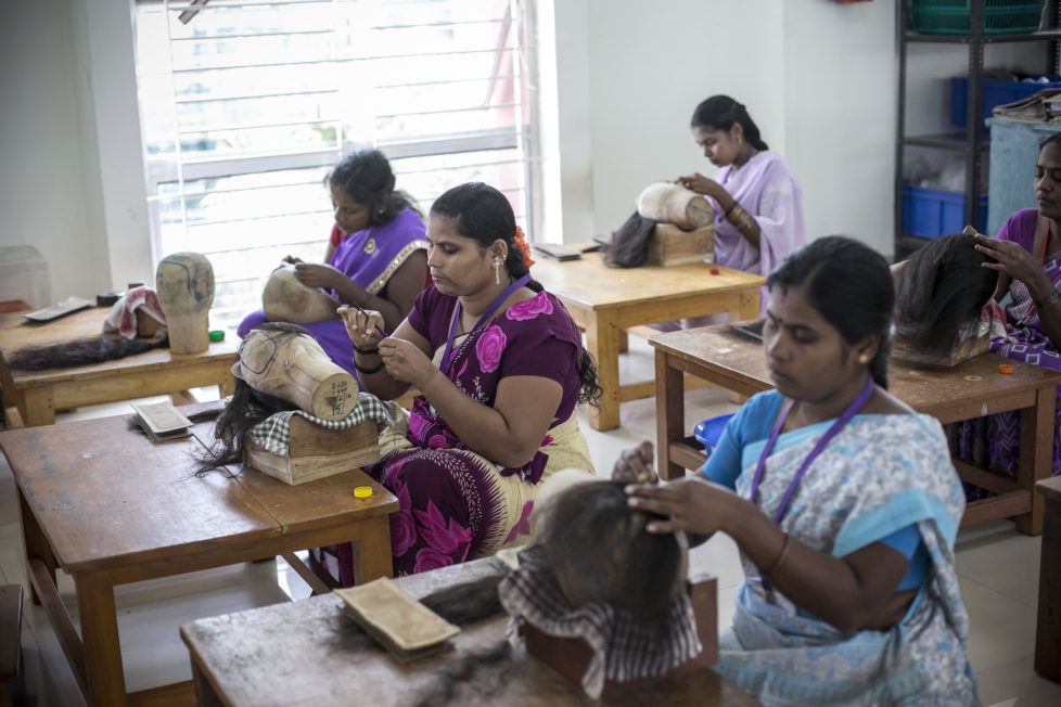 "CHENNAI, INDIA - NOVEMBER 11: Workers hand make wigs at Raj Hair International November 11, 2016 in Thiruttani, India. Raj Hair International donates wigs to cancer patients in India and also exports hair products, including weaves and wigs, to 56 countries. All of the hair they export comes from Tamil Nadu, 1/4 of which is temple hair and the rest comes from comb waste that people sell. They estimate that it takes 1 full month to make one wig by hand. The process of shaving ones hair and donating it to the Gods is known as tonsuring. It is common for Hindu believers to tonsure their hair at a temple as a young child, and also to celebrate a wish coming true, such as the birth of a baby or the curing of an illness. The ""temple hair"", as it's known, is then auctioned off to a processing plant and then sold as pricey wigs and weaves in the US, Europe and Africa. (Photo by Allison Joyce/Getty Images)"