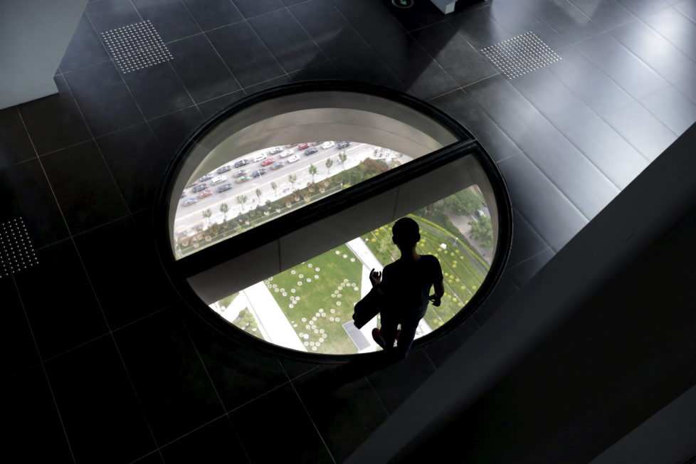 A man stands on the glass floor area constructed as a view point on 37th floor of the China Central Television (CCTV) Tower in Beijing, June 11, 2015. REUTERS/Jason Lee - RTX1G35V
