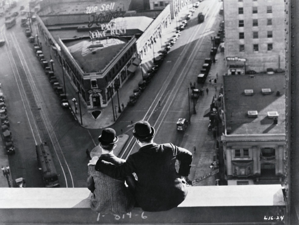 Comedy team Laurel and Hardy sitting atop building scaffolding, look down on city street in film scene from the 1920s.