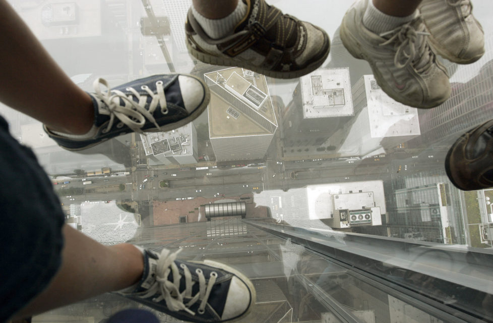 "Children stand on ""The Ledge"" and look down through a glass floor 1,353 feet (412 meters) above Wacker Drive in Chicago July 1, 2009. The Ledge is part of Skydeck Chicago located on the 103rd floor of the Sears Tower. It opens to the public on July 2. REUTERS/Frank Polich (UNITED STATES SOCIETY IMAGES OF THE DAY) - RTR258BY"