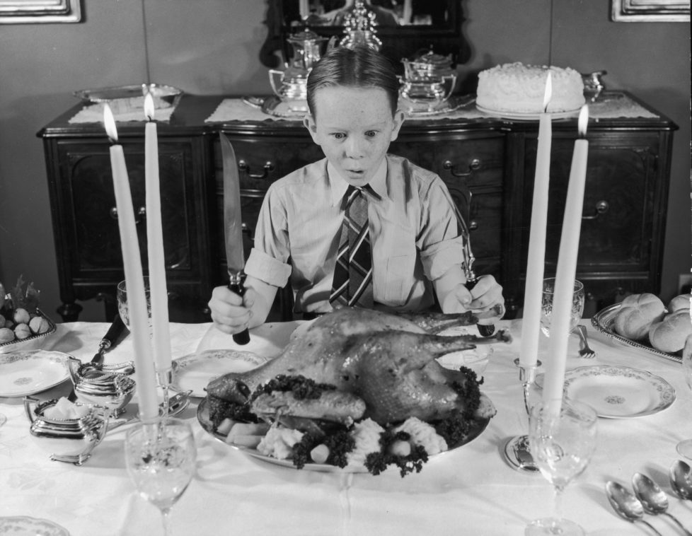 circa 1955: A freckle-faced boy sitting at the Thanksgiving dinner table gasps in awe at the roasted turkey, as he clutches carving utensils. (Photo by Lambert/Getty Images)