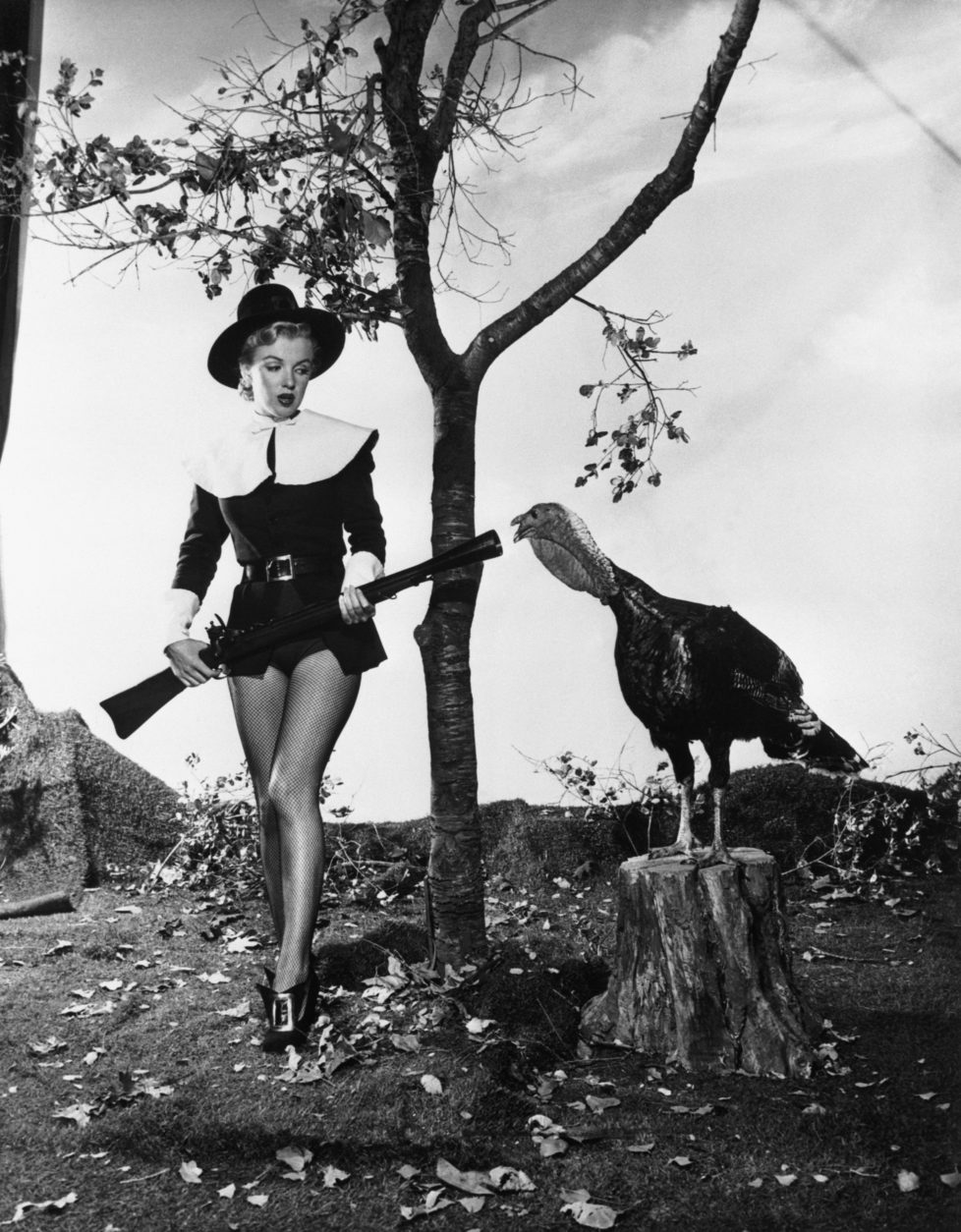 """(Original Caption) 11/10/1950-Hollywood, California- Wearing a costume that is half-Puritan, half-chorine, pretty Marilyn Monroe seems to have little desire to hunt turkey after finding this gobbler, still """"stumping"""" long after Election Day. Currently seen in """"All About Eve,"""" this movie starlet seems just as frightened by the gun as the bird is."""