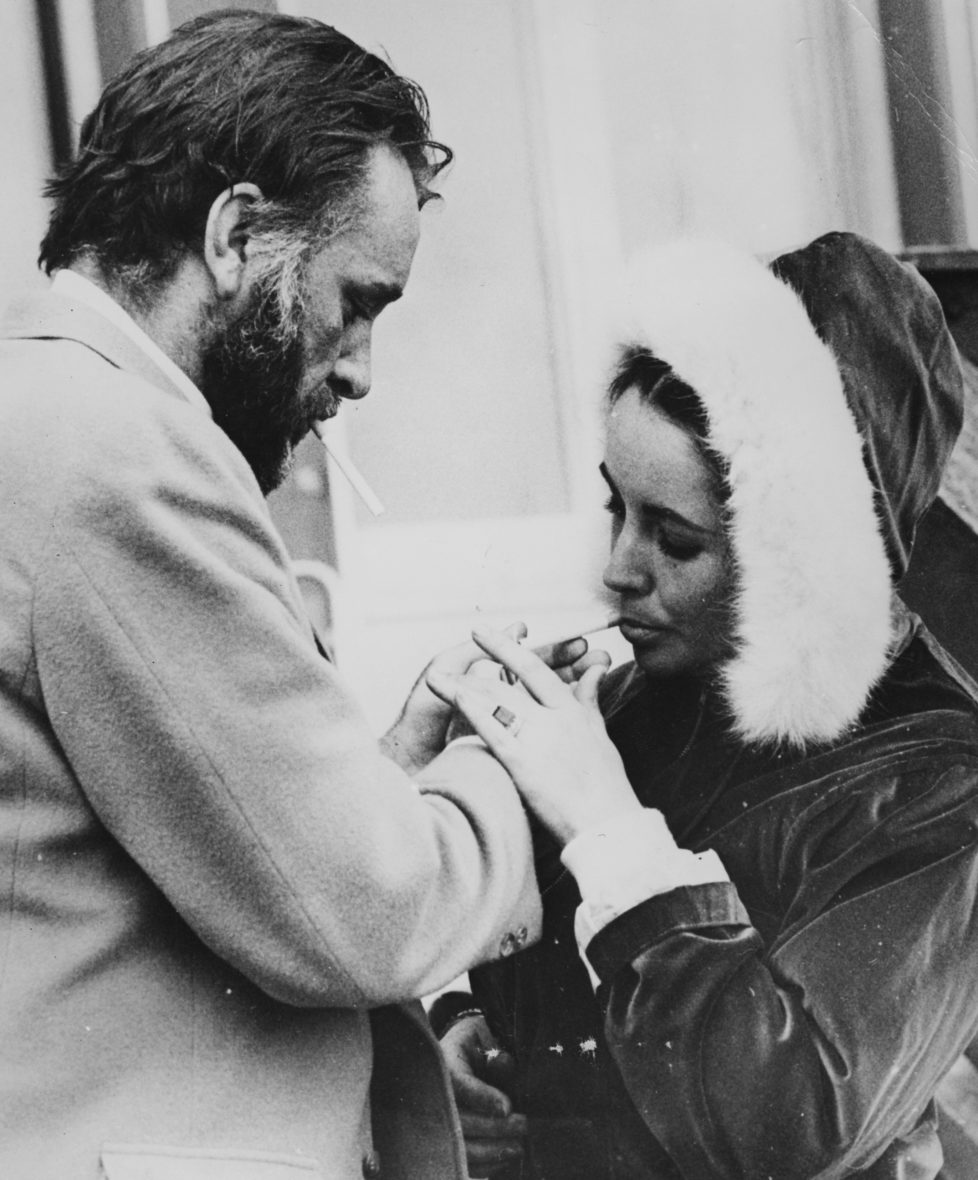 Actor Richard Burton lighting a cigarette for his wife Elizabeth Taylor, outside their chalet in Gstaad, March 7th 1966. (Photo by Central Press/Hulton Archive/Getty Images)