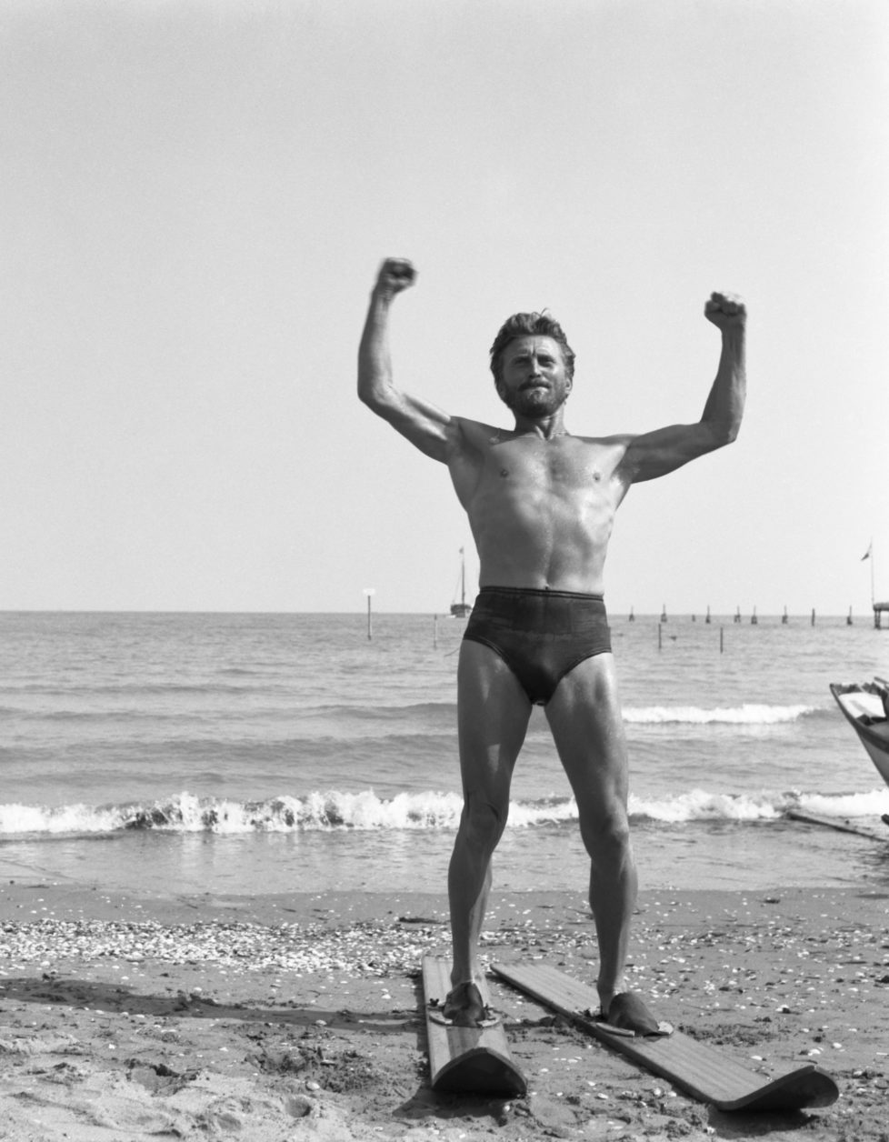 American actor Kirk Douglas, wearing a swimming suit and a necklace chainlet, portrayed while wearing a pair of waterski, on the Lido beach, Venice 1953. (Photo by Archivio Cameraphoto Epoche/Getty Images)