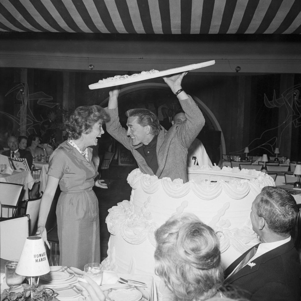 """(Original Caption) 4/24/1959-Palm Springs, California- Shrieking with delight, Anne Douglas does a double-take as her actor husband Kirk Douglas pops up out of a giant birthday cake. Douglas, wearing his hair long for his role in """"Spartacus,"""" came secretly from Hollywood and hid out in the cake to surprise his wife at her birthday party at the Howard Manor."""